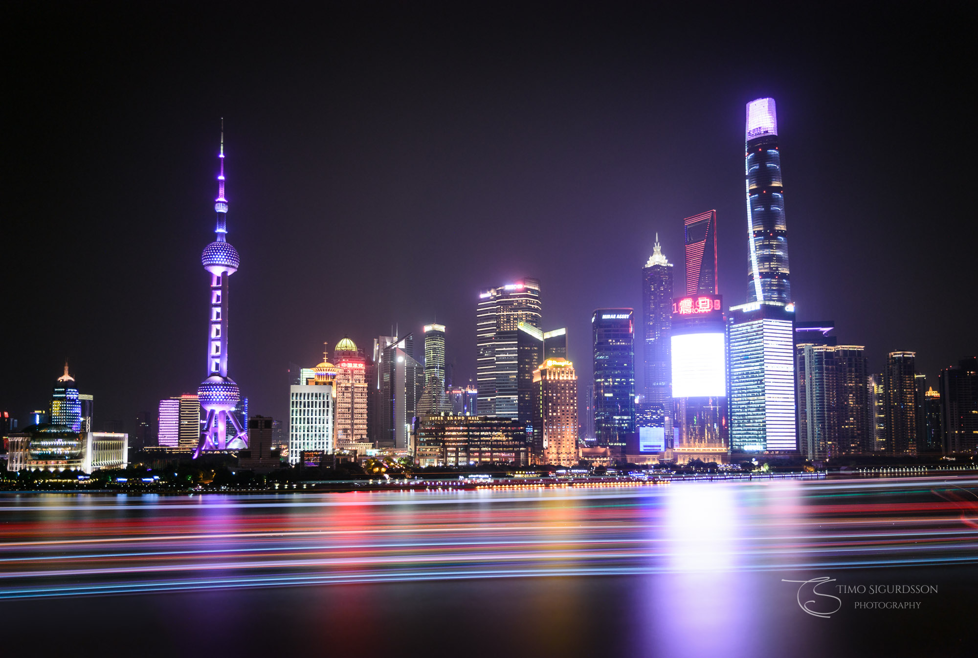Pudong, Shanghai, China. Skyline at night behind Huangpu river.