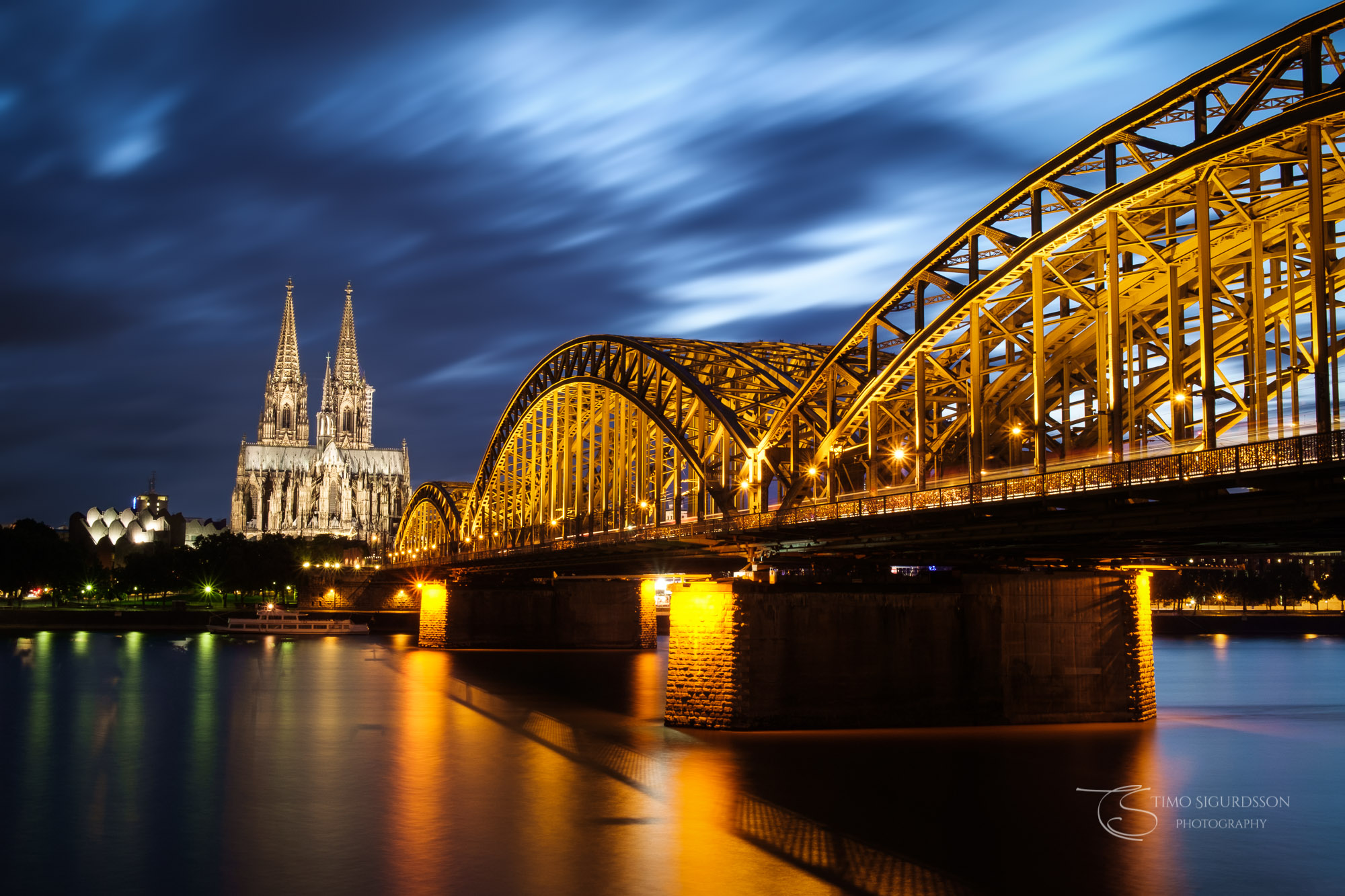 Cologne | Köln, Germany. Cathedral and Hohenzollern bridge at night. River Rhine.
