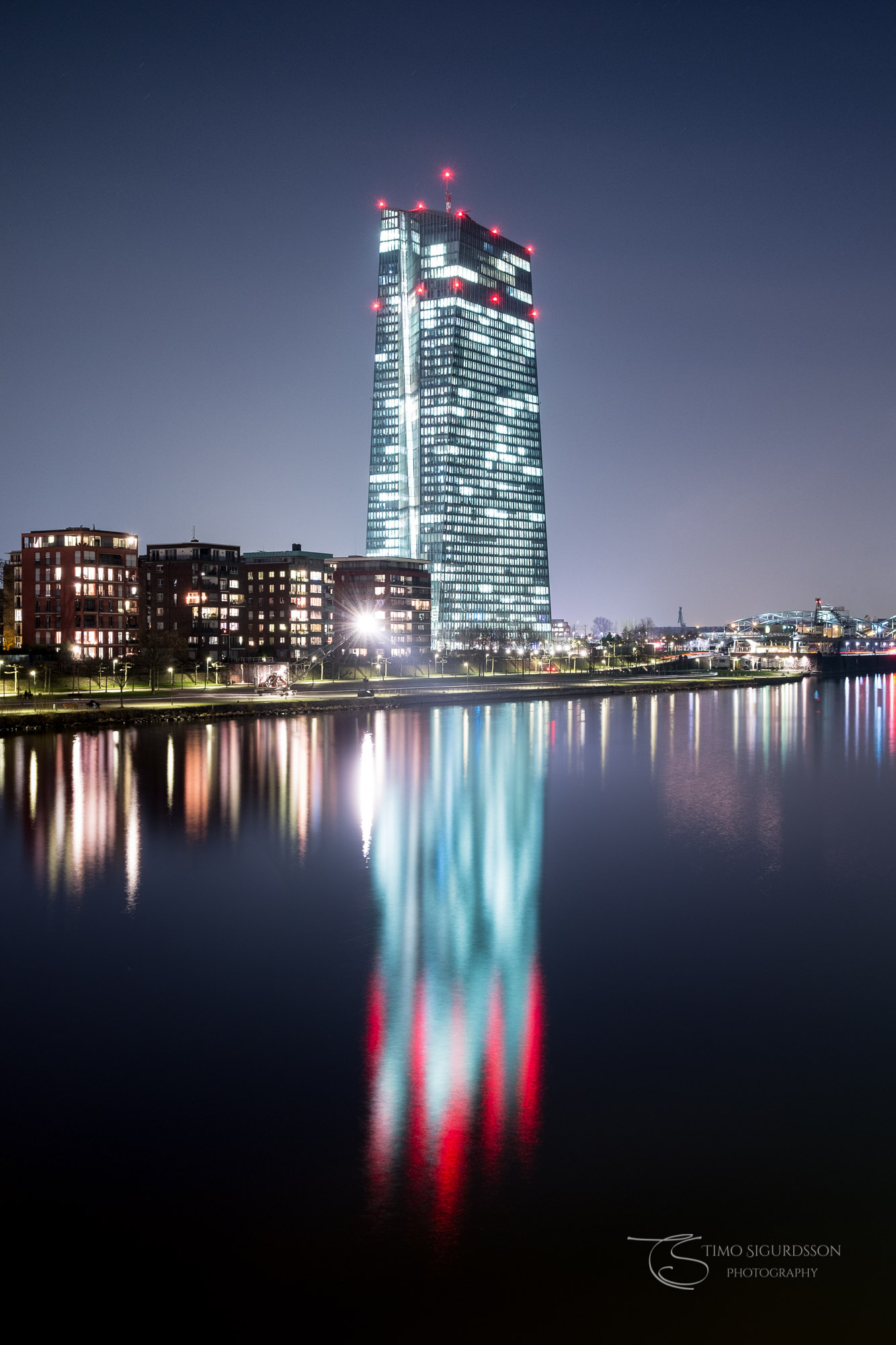 Ostend, Frankfurt. European Central Bank at night. Reflection in river Main.