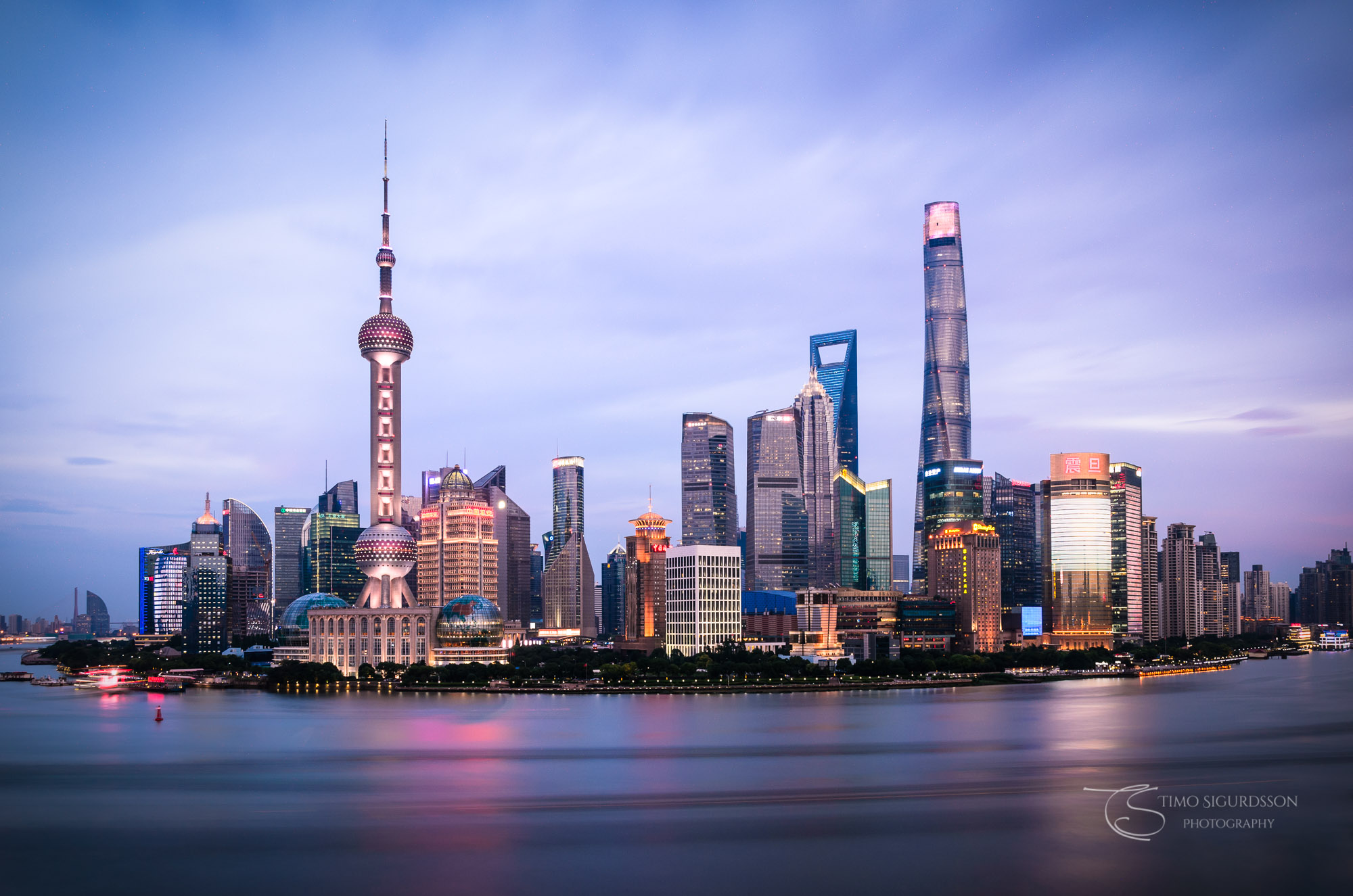 Shanghai, China. Pudong skyline at dusk. Huangpu river.